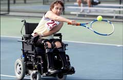 Woman in a power wheelchair playing tennis